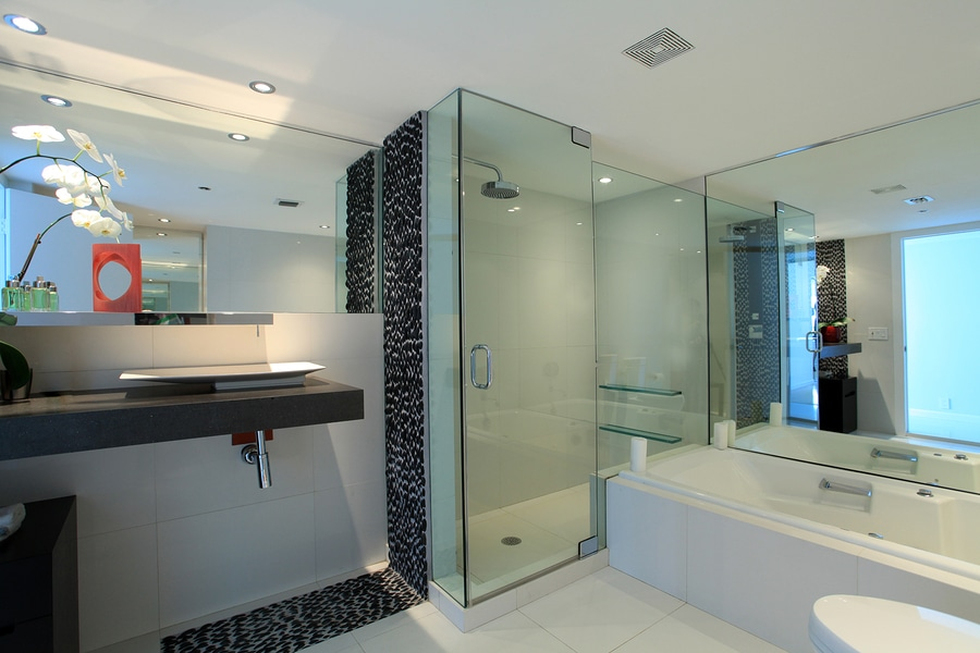 Luxury bathroom details of stone, tile, and glass doors.